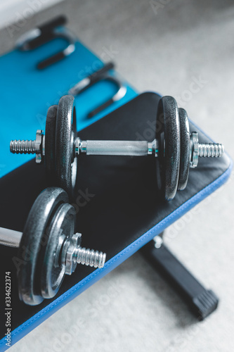 Fototapeta home gym concept, room with dumbbells on gym bench and push-up handles on yoga mat to workout from home obraz