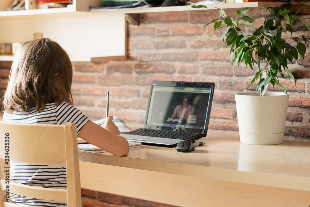 Fototapeta The concept of distance online learning self-isolation. Child sitting home desk doing lessons through a digital laptop.