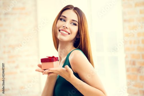 Young happy smiling attractive woman with gifts, at home, indoors Canvas Print