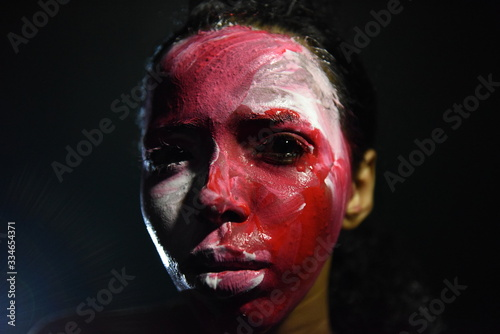 Beauty model girl with colorful paint on her face