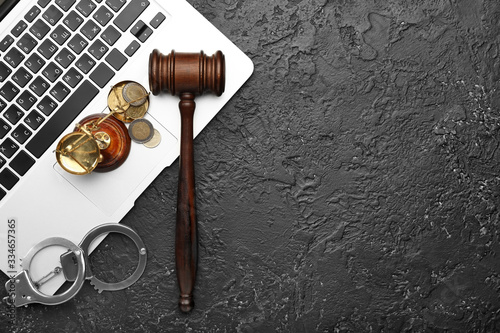 Photo Judge's gavel, laptop, scales of justice and handcuffs on dark background