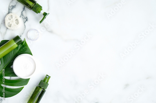 SPA natural organic cosmetic products with monstera tropical plant leaves on marble background Canvas Print