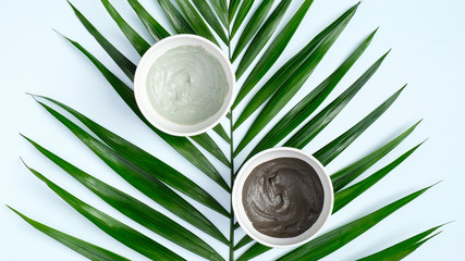 Top view clay masks and tropical leaf. Natural SPA cosmetics for skincare, bo...