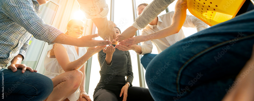 Fototapeta business teamwork relationship ideas concept Close up worm eye view of young people putting their hands together. Friends with stack of hands showing unity and teamwork.