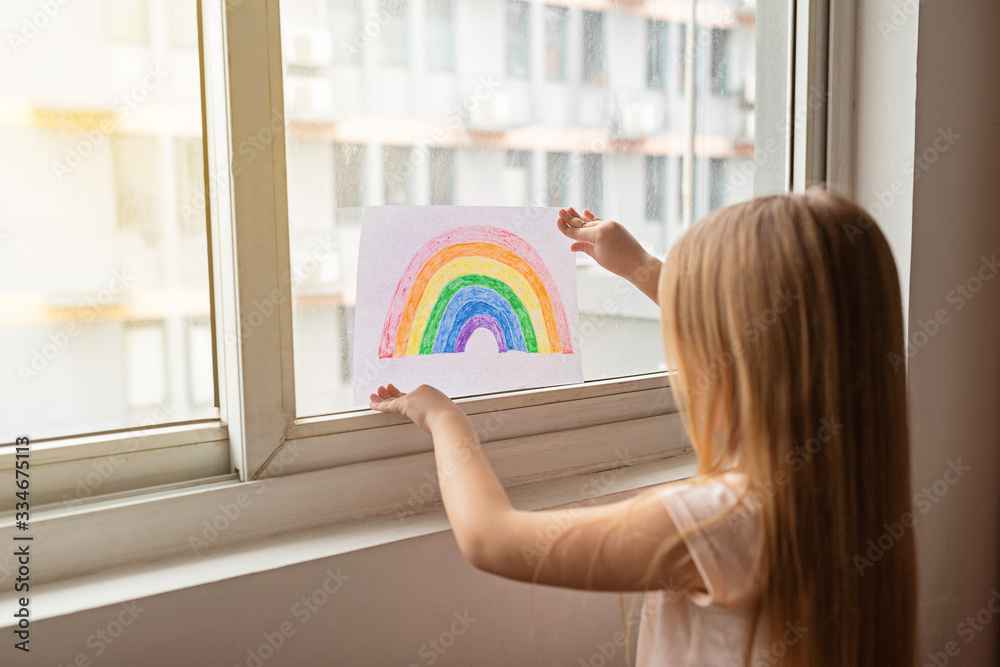Fototapeta Kid painting rainbow during Covid-19 quarantine at home. Girl near window. Stay at home Social media campaign for coronavirus prevention, let's all be well, hope during coronavirus pandemic concept