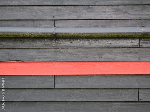 black painted wooden wall of a barn with one red stripe and a drainpipe Canvas Print