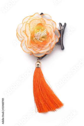 Obraz na plátně Subject shot of a metal hair clips with serrated edges and decorated with a creamy-orange fabric flower with an orange silky tassel