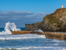 A Large Wave Hitting The Coast At Portreath, Cornwall, With The Cliffs In The Background
