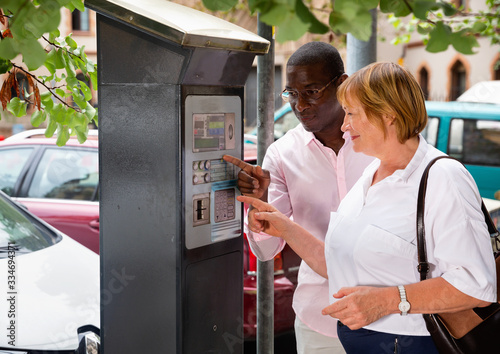 Fototapeta Polite intelligent African man helping middle aged woman to buy ticket in parking meter on summer city street obraz