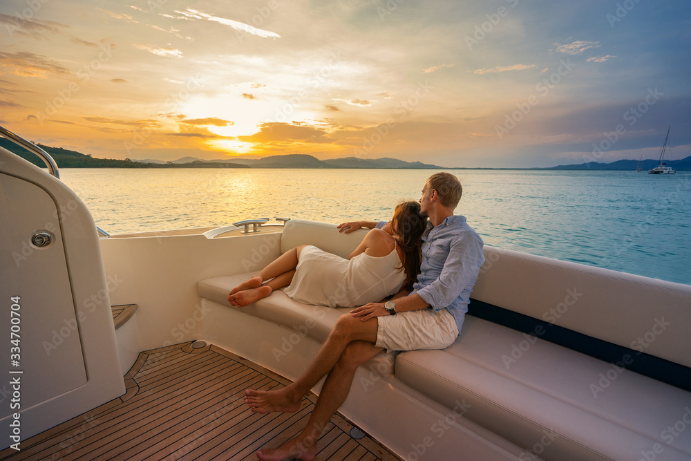 Fototapeta Romantic vacation . Beautiful couple looking in sunset from the yacht.