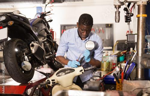Photo Male afro american worker repairing scooter in motorcycle workshop
