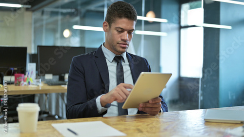 Young African Businessman Writing on Paper on Office Desk