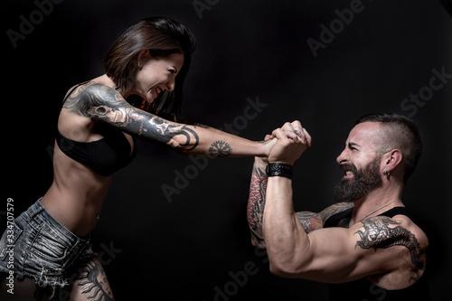 coppia di ragazzi tatuati, fanno un aprova di forza, , isolati su sondo nero Canvas Print