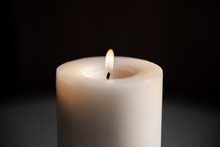 Big White Candle On A Dark Background