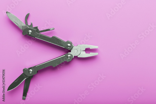 Fotografie, Tablou Multitool is a multi-functional tool on a pink background