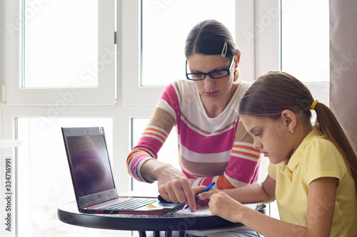 A home tutor teaches a child sitting at a table and using a computer Canvas Print