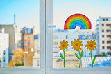 Fototapeta Tęcza - Colorful rainbow and yellow flowers painted on window glass in Parisian apartment