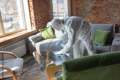 Obraz Coronavirus Pandemic. A disinfector in a protective suit and mask sprays disinfectants in house or office. Protection agsinst COVID-19 disease. Prevention of spreding pneumonia virus with surfaces. - fototapety do salonu