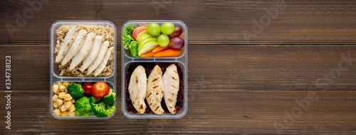 Fotografie, Obraz Clean healthy low fat food in two takeaway meal box sets on wood banner backgrou