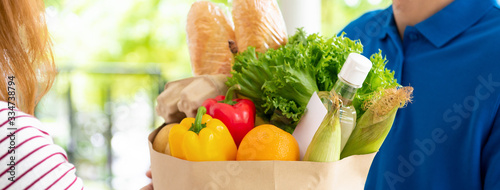 Fototapeta Grocery store delivery man in blue uniform delivering food to a woman customer at home, banner size obraz