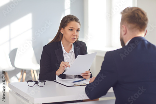Fototapeta Woman employer talking interviews a man for a job vacancy in a company obraz