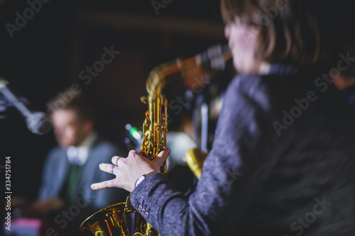 Fotografie, Tablou Concert view of a female saxophonist,  professional saxophone player with vocali
