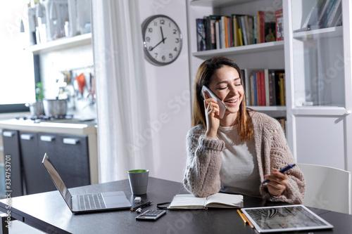 Valokuva Giovane donna pratica lo smart working da casa, e parla al telefono sorridendo ,