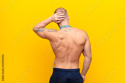 Photo young strong blonde man thinking or doubting, scratching head, feeling puzzled a