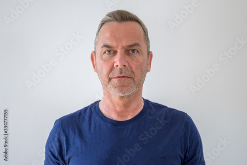 Fotografie, Tablou Bust portrait of middle-aged man in blue t-shirt