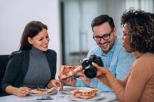 Friends Having Sharing Pizza And Having Fun, Looking At Photos On Camera.