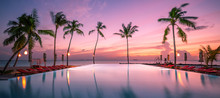 Beautiful Poolside And Sunset Sky With Palm Trees Silhouette. Luxurious Tropical Beach Landscape, Deck Chairs And Loungers And Water Reflection. Tranquil Summer Vacation, Travel Concept Infinity Pool