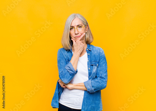 Fotografia senior or middle age pretty woman looking serious, thoughtful and distrustful, w