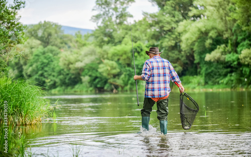Obraz Calling Fly-Fishing a hobby. fisherman with fishing rod. retired bearded fisher. Trout bait. hobby and sport activity. mature man fly fishing. man catching fish. summer weekend. Big game fishing - fototapety do salonu