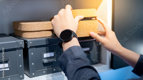 Obraz Male hand opening empty brown cork board box. Packaging design for home decoration or office supplies. - fototapety do salonu