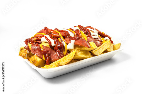 Fototapeta Peruvian street food:  Classic salchipapas or sausages and french fries  with ketchup, mustard, mayonnaise and chili peppers served on a white plate obraz