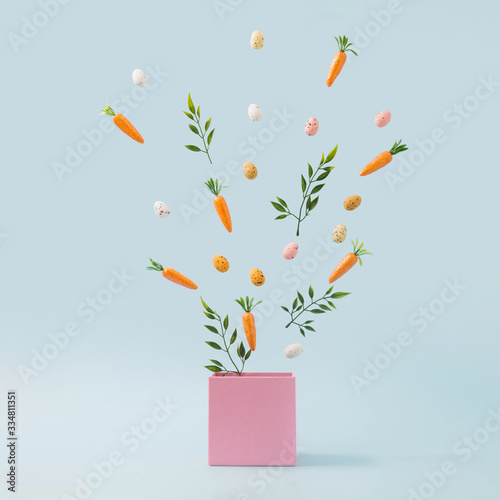 Spring leaves, Easter eggs and carrots coming out of pink box. Spring nature concept. Easter holiday background idea. Fotomurales
