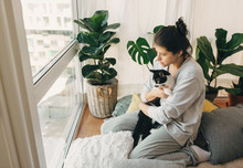 Sad Girl Hugging Cute Cat, Sitting Together At Home During Coronavirus Quarantine. Stay Home Stay Safe. Isolation At Home To Prevent Virus Epidemic. Young Woman With Cat In Modern Room