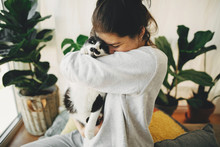 Happy Hipster Girl Hugging Cute Cat, Sitting Together At Home During Coronavirus Quarantine. Stay Home Stay Safe. Isolation At Home To Prevent Virus Epidemic. Young Woman With Cat In Modern Room