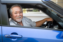 Asian Senior Man Driving A Car...