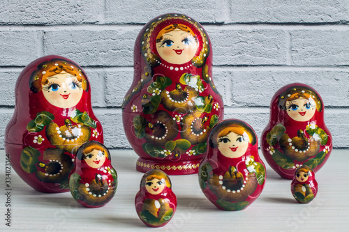 Fotografia, Obraz A set of bright red wooden lacquered nesting dolls on a white wooden table close