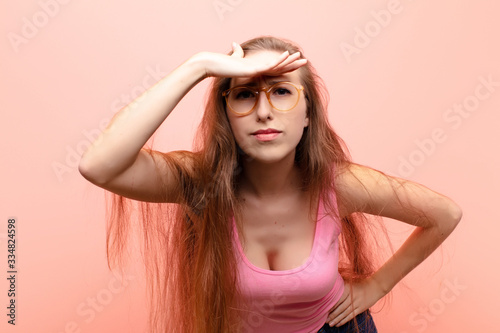 yound blonde woman looking bewildered and astonished, with hand over forehead lo Wallpaper Mural