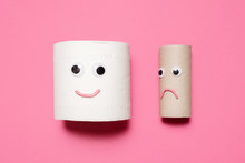Happy Smiling Full Toilet Paper Roll Next To A Sad And Frowning Empty Toilet Paper Roll Looking At It With Googly Eyes And Mouth On A Pink Background With Copy Space And Room For Text