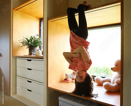 Fotografija Ein Mädchen hängt während der Coronakrise gelangweilt kopfüber am Fenster am 01