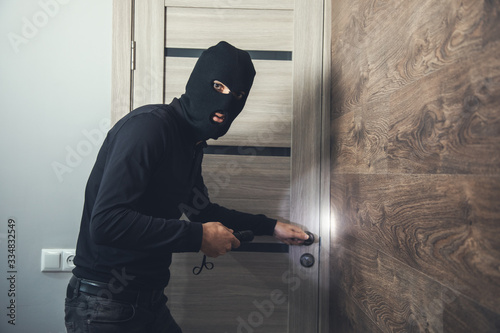 Cuadros en Lienzo burglar sneaking into the house with flashlight
