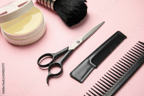 Professional hairstyling tools on light pink background