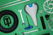 Set of different bicycle tools and parts on green background, flat lay