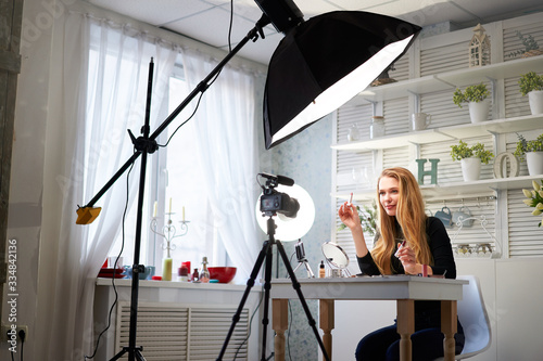 Beauty blogger woman filming daily make-up routine tutorial on camera. Influencer blonde girl live streaming cosmetics product review in home studio with professional lighting equipment. Vlogger job.
