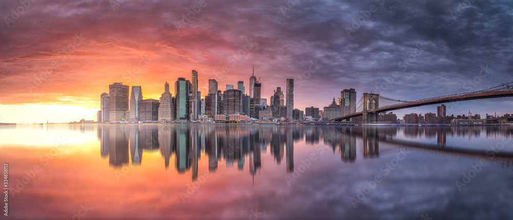 Fototapeta New york skyline reflection on the Hudson river at Brooklyn bridge at sunset