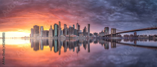 New york skyline reflection on the Hudson river at Brooklyn bridge at sunset