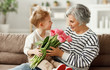 Cheerful little boy giving flowers to grandmother.